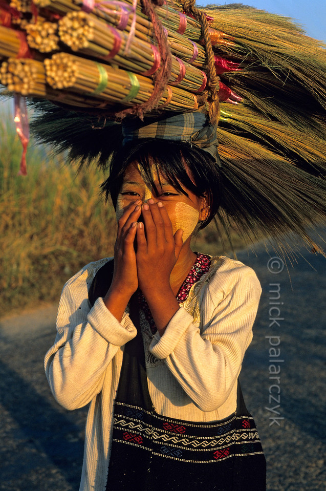 [BURMA 24.748] 'Girl with brooms.'  On a Burmese road north of Taungoo, this girl is surprised and somewhat shy when she is photographed. She has a bundle of brooms on her head, to be sold at the market where she is heading. Her cheeks are enlivened by thanaka, a yellow paste made of pulverized tree-bark, used by many Burmese women and some men as well as a combination of sun block and make-up. Photo Mick Palarczyk.
