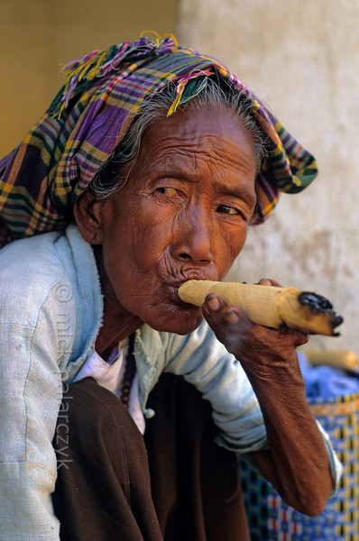 [BURMA 24.902] 'Smoking a cheroot.'  At Nyaung U on the Bagan plain, an old woman is smoking a cheroot in the courtyard of the Shwezigon Pagoda. Cheroots are very mild Burmese cigars that contain only a small amount of tobacco mixed with other leaves, roots and herbs. Photo Mick Palarczyk.