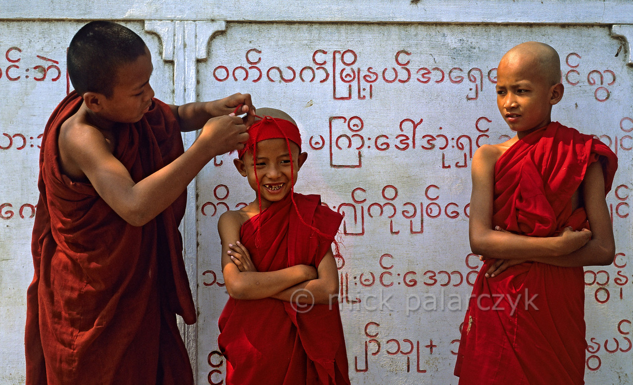 [BURMA 25.041] 'Young monks at Sagaing.'  These young monks are standing in front of a slab that records the names of people that have donated money to local temples at the foot of Sagaing Hill. Photo Mick Palarczyk.