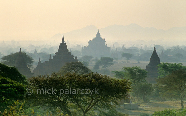 [BURMA 24.918] 'The Bagan plain in morning mist.'  	Surrounded by other temples, the 12th century Sulamani Temple (centre) can be seen appearing from a morning haze. The horizon of this view is formed by the hills around Mount Popa. Photo Mick Palarczyk.