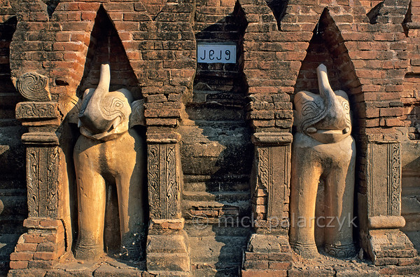 [BURMA 24.908] 'Elephants.'  	Elephant sculptures adorning the base of a small stupa north of the road between Bagan village and Nyaung U. White elephants hold a special place in Buddhism. According to myth Buddha was fathered by such an animal as it visited his mother in a dream. Photo Mick Palarczyk.