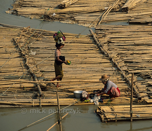 [BURMA 25.077] 'Bamboo raft at Mandalay.'  	At Mandalay women are washing clothes in the Irrawaddy on a raft of bamboo poles that has been transported downstream. They are part of a workforce that is about to dismantle the raft and carry the poles to the embankment. Photo Mick Palarczyk.