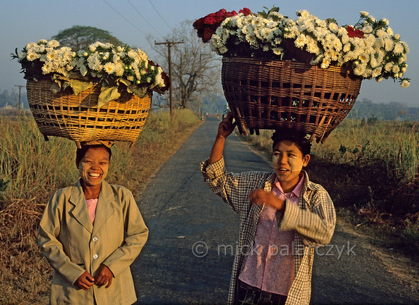 [BURMA 24.743] 'Carrying flowers.'  	North of Taungoo two women are on their way to sell flowers at the market. Photo Mick Palarczyk.