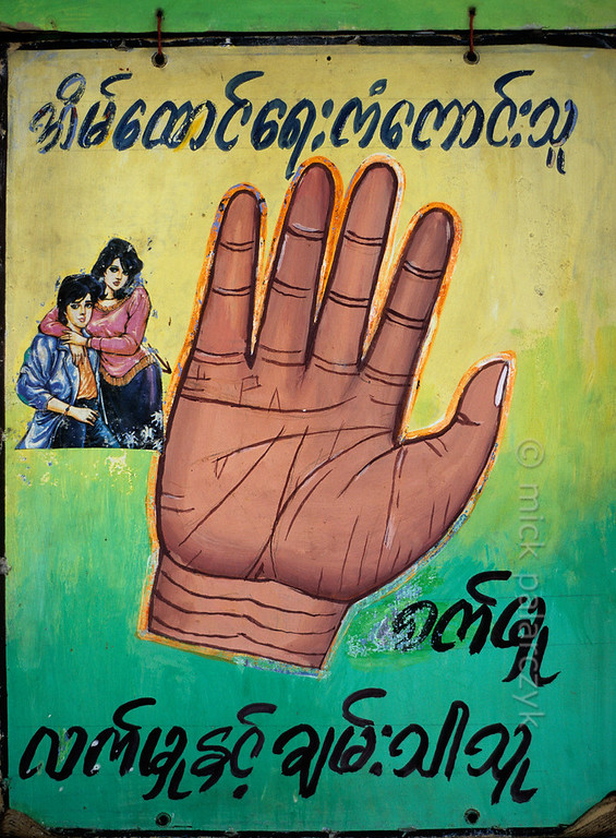 [BURMA 24.707] 'Fortune-teller's poster.'  A poster of a palm-reading fortune-teller at Yangon's Chaukhtatgyi Pagoda promises good advice in matters of love and relations. Photo Mick Palarczyk.