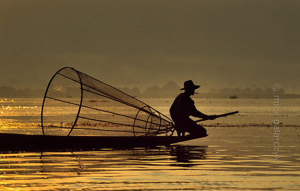 [BURMA 24.831] 'Searching for fish.'  	While the first sun-rays are piercing the haze over the Inle Lake, an Intha fisherman searches the lake for a catch. Photo Mick Palarczyk.
