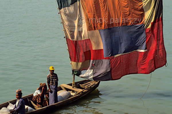 [BURMA 24.980] 'Sailing on the Chindwinn River.'  	At Monywa, a boat on the Chindwinn River carries a sail which has been sewn together from different pieces of colourful cloth. The Chindwinn is a tributary of the Irrawaddy. Photo Mick Palarczyk.