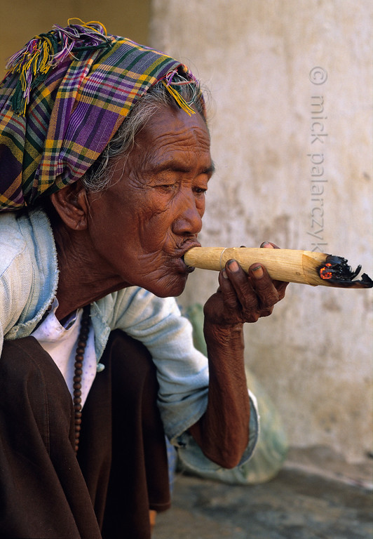 [BURMA 24.904] 'Smoking a cheroot.'  At Nyaung U on the Bagan plain, an old woman is smoking a cheroot in the courtyard of the Shwezigon Pagoda. Cheroots are very mild Burmese cigars that contain only a small amount of tobacco mixed with other leaves, roots and herbs. Photo Mick Palarczyk.