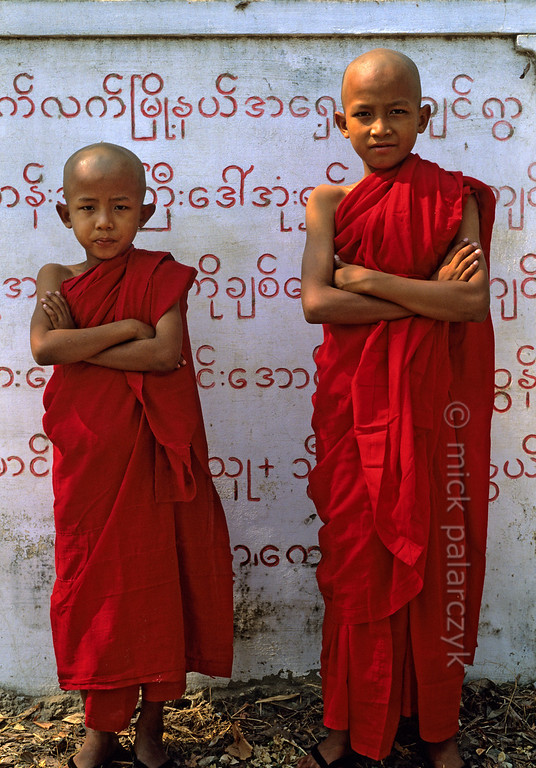 [BURMA 25.043] 'Young monks at Sagaing.'  	These young monks are standing in front of a slab that records the names of people that have donated money to local temples at the foot of Sagaing Hill. Photo Mick Palarczyk.