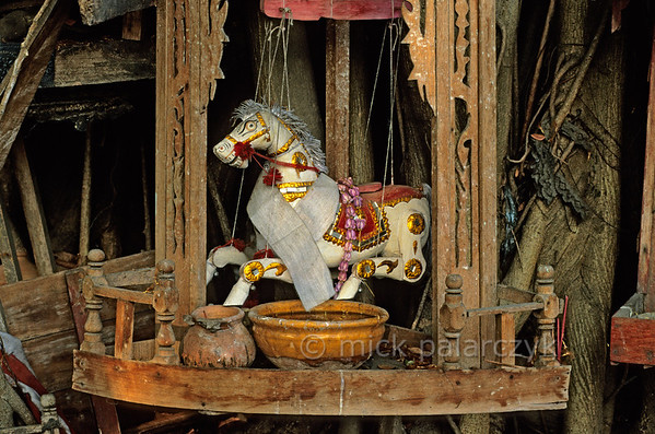 [BURMA 24.704] 'Horse spirit.'  	Along Strand Road in Yangon a bowl of water stands as an offering in a small tree-shrine of a horse nat (spirit). The spirit which dwells in the tree is personified by a marionette. Photo Mick Palarczyk.