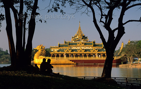 [BURMA 24.667] 'Kandawgyi Lake.'  The shores of the Kandawgyi Lake near the centre of Burma's former capital Yangon are a favourite leisure spot for the citizens of the town. They enjoy the view of the Karaweik Restaurant, a non-floating reproduction of an ancient royal barge. Photo Mick Palarczyk.