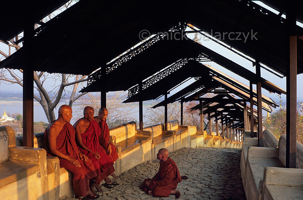 [BURMA 25.031] 'Covered stairway at Sagaing.'  	Covered stairways connect the numerous monasteries and temples that dot the Sagaing hills on the western bank of the Irrawaddy River. The benches that line these stairs are pleasant resting places for the resident monks climbing up and down the hills. Photo Mick Palarczyk.