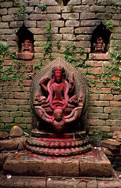 [NEPAL.KATHMANDUVALLEY 27367] 'Vishnu in Kirtipur.'  Covered in red powder, Vishnu rides the mythical birdman Garuda in a small street shrine in Kirtipur, southwest of Kathmandu. Red powder has been smeared on the sculpture during puja offerings. Photo Mick Palarczyk & Paul Smit.