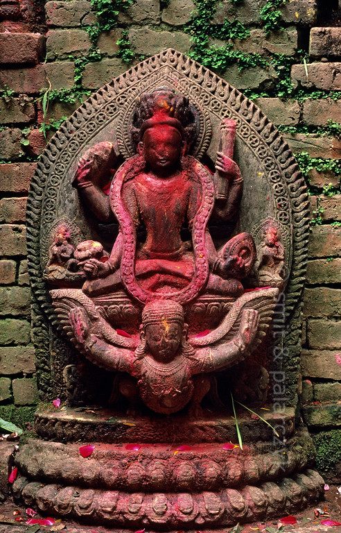 [NEPAL.KATHMANDUVALLEY 27366] 'Vishnu in Kirtipur.'  	Covered in red powder, Vishnu rides the mythical birdman Garuda in a small street shrine in Kirtipur, southwest of Kathmandu. Red powder has been smeared on the sculpture during puja offerings. Photo Mick Palarczyk & Paul Smit.