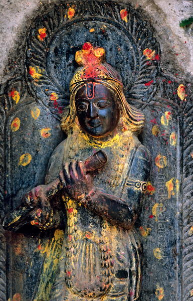 [NEPAL.KATHMANDUVALLEY 27278] 'Krishna playing the flute.'  	This statue of Krishna playing the flute can be found on Kathmandu's Pachali Ghat, along the Bagmati River. Yellow and red powder has been smeared on the sculpture during a puja offering. Photo Mick Palarczyk.