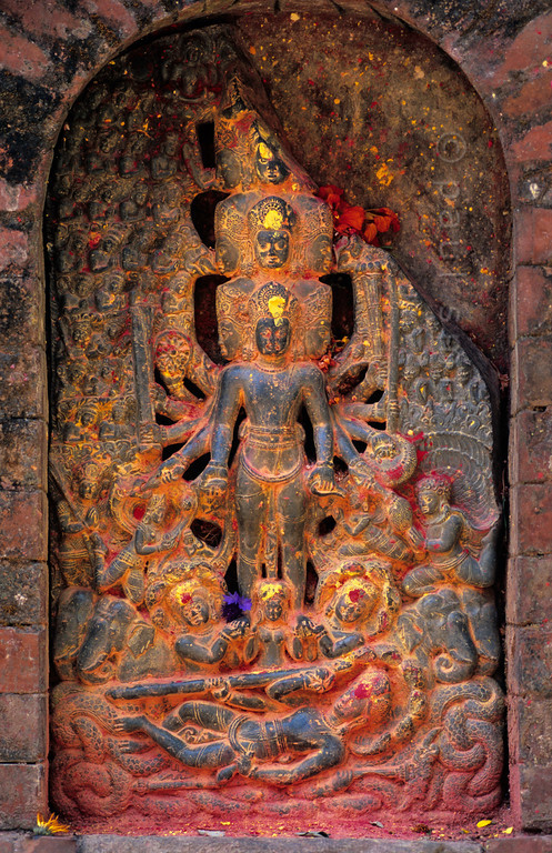 [NEPAL.KATHMANDUVALLEY 27563] 'Vishnu at Changu Narayan.'  	A relief from the 8th century AD shows Vishnu Vishwarup (Vishnu in his Universal Form) reclining on the snake of infinity in the ocean of existence. Above that, the god rises from the waters with his thousend heads and arms symbolizing omnipotence. The relief can be found on the grounds of the Vishnu Temple at Changu Narayan. Red and yellow powder has been smeared on it during puja offerings. Photo Paul Smit.