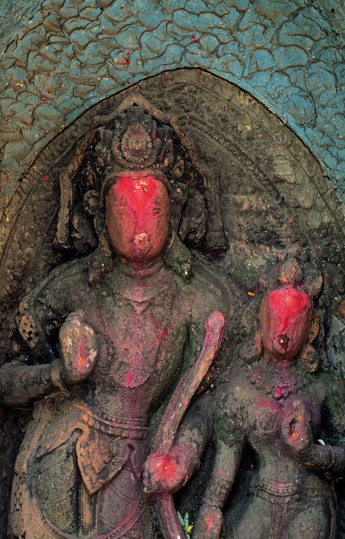 [NEPAL.KATHMANDUVALLEY 27428] 'Shiva on Bhaktapur's Hanuman Ghat.'  	This statue of Shiva, the Hindu God of Destruction, holding his divine bow, is located on Bhaktapur's Hanuman Ghat. Red powder has been smeared on the sculpture during puja offerings. Photo Paul Smit.