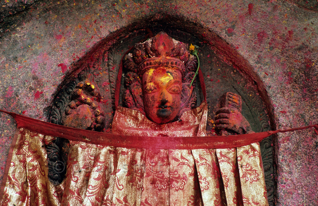 [NEPAL.KATHMANDUVALLEY 27524] 'Shiva behind curtain.'  	A statue of Shiva in Thimi is partly hidden by a curtain. Red and yellow powder has been smeared on the sculpture during puja offerings. Photo Paul Smit.