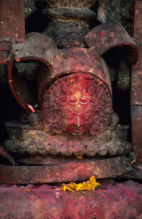 [NEPAL.KATHMANDUVALLEY 27287] 'Bell at Kathmandu's shrine of Pachali Bhairava.'  	The top of a bell at Kathmandu's shrine of Pachali Bhairava is decorated with the head of Bhairava.  Bhairava is the fierce manifestation of Shiva, associated with annihilation and the march of time. He can be identified here by his bulging eyes, his mustache and the crescent moon of Shiva on his forehead. Yellow flowers have been offered to the god during a puja offering. Photo Paul Smit.
