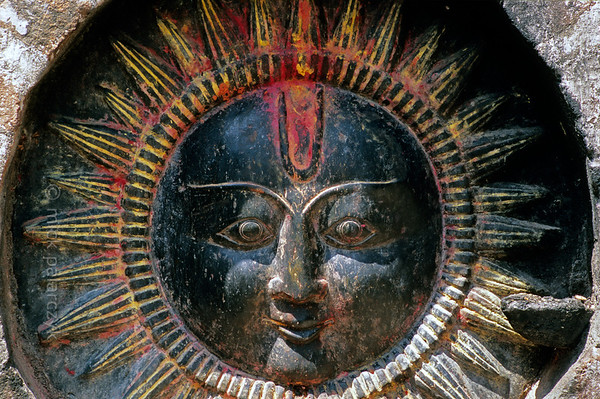 [NEPAL.KATHMANDUVALLEY 27280] 'Sunny face.'  One of the many reliefs and statues which can be found on Kathmandu's Pachali Ghat is this anthropomorphic sundisc, the sun god Surya. Yellow and red powder has been smeared on the relief during a puja offering. Photo Mick Palarczyk.