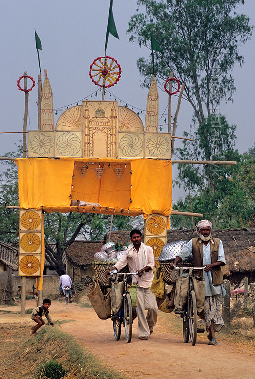 [NEPAL 27584] 'Festival gate near Nepalganj.'  	In a Terai village just north of Nepalganj, two pedlars, their bicycles packed with pots and pans, have just past the gaudy gate of a local festival. Photo Mick Palarczyk.