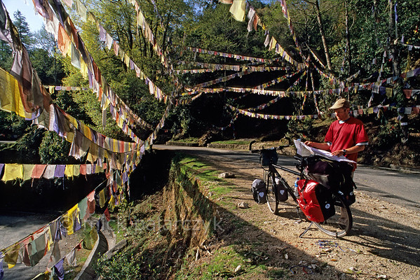 [NEPAL 27603] 'Prayer flags over the Tribhuwan Highway.'  Between Daman and the Simbhanjyang Pass the Tribhuwan Rajpath (highway) snakes its way up past the Shri Rikheshwar Temple. The switchback near the temple passes under a multitude of prayer flags. Photo Mick Palarczyk.