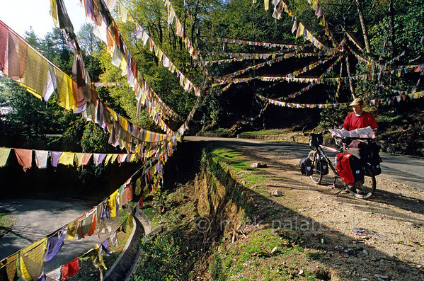 [NEPAL 27607] 'Prayer flags over the Tribhuwan Highway.'  Between Daman and the Simbhanjyang Pass the Tribhuwan Rajpath (highway) snakes its way up past the Shri Rikheshwar Temple. The switchback near the temple passes under a multitude of prayer flags. Photo Mick Palarczyk.
