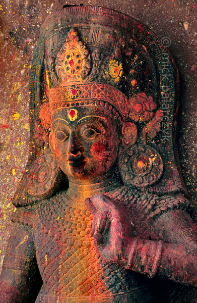 [NEPAL.KATHMANDUVALLEY 27569] 'Bhimsen at Sankhu.'  At Sankhu fresh offerings of red and yellow powder create a beautiful combination with older powder-offerings that have been washed out by the rain on this roadside statue of Bhimsen, the patron deity of Newar shopkeepers. Photo Mick Palarczyk.