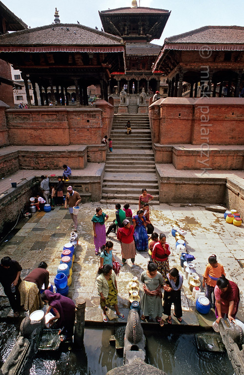 [NEPAL.KATHMANDUVALLEY 27325] 'Tapping water on Patan's Durbar Square.'  	In the early morning women and girls tap water at Manga Hiti, a sunken well and watertank at the northern end of Patan's Durbar Square. The stairs to the tank are flanked by two pavilions, the right one of which houses a royal throne (see picture 27323). Behind the pavilions rises the Bishwanath Temple (dedicated to Shiva). Photo Mick Palarczyk.