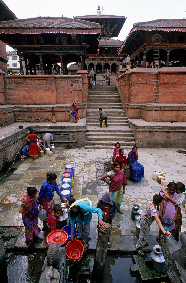 [NEPAL.KATHMANDUVALLEY 27326] 'Tapping water on Patan's Durbar Square.'  In the early morning women and girls tap water at Manga Hiti, a sunken well and watertank at the northern end of Patan's Durbar Square. The stairs to the tank are flanked by two pavilions, the right one of which houses a royal throne (see picture 27323). Behind the pavilions rises the Bishwanath Temple (dedicated to Shiva). Photo Mick Palarczyk.