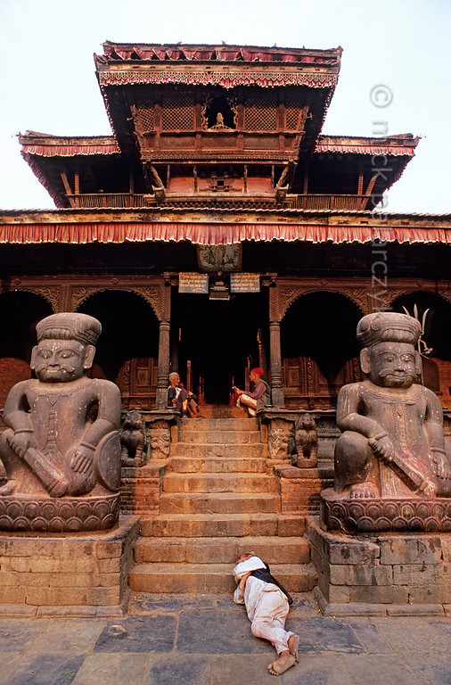 [NEPAL.KATHMANDUVALLEY 27407] 'Guarded by wrestlers.'  	Guarded by the statues of the two famous wrestlers Jaya Malla and Patha Malla an old man takes a nap in front of Bhaktapur's Dattatraya Temple, which is frequented by Hindus as well as Buddhists.  Photo Mick Palarczyk.