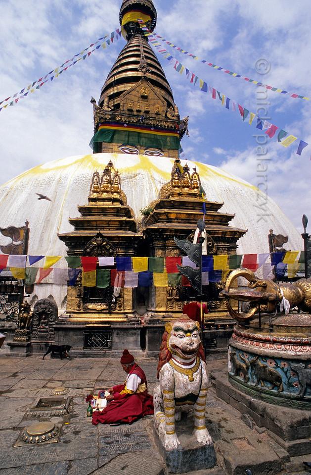 [NEPAL.KATHMANDUVALLEY 27223] 'Monk at Swayambhu.'  At the foot of Swayambhu stupa, west of Kathmandu, a Buddhist monk is reciting prayers. Photo Mick Palarczyk.