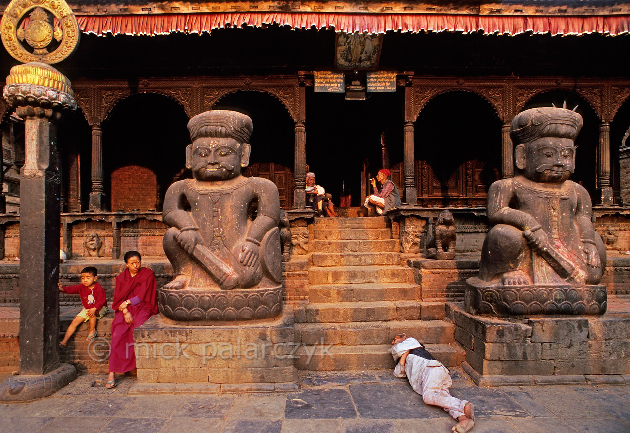 [NEPAL.KATHMANDUVALLEY 27404] 'Guarded by wrestlers.'  Guarded by the statues of the two famous wrestlers Jaya Malla and Patha Malla an old man takes a nap in front of Bhaktapur's Dattatraya Temple, which is frequented by Hindus as well as Buddhists.  Photo Mick Palarczyk.
