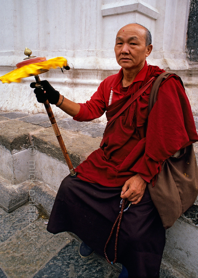 [NEPAL.KATHMANDUVALLEY 27222] 'Pilgrim at Swayambhu.'  	Twirling his hand-held prayer wheel, a Buddhist pilgrim takes a rest near the stupa of Swayambhu, west of Kathmandu. Photo Mick Palarczyk.