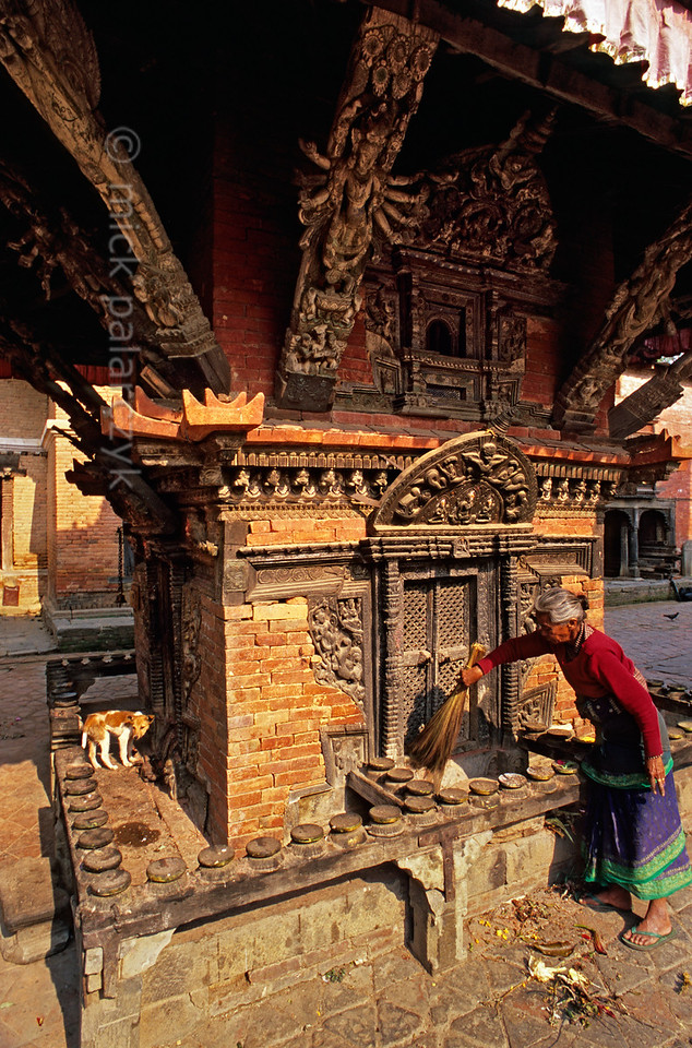 [NEPAL.KATHMANDUVALLEY 27559] 'Morning clean up in Changu Narayan.'  An old woman is sweeping away the remnants of puja offerings from the Pashupatinath Shrine in the courtyard of Vishnu Temple  at Changu Narayan. Photo Mick Palarczyk.