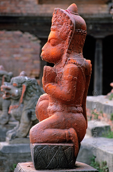 [NEPAL.KATHMANDUVALLEY 27415] 'Hanuman on Bhaktapur's Maheshwari Ghat.'  A statue of the Hindu ape-god Hanuman has been smeared with orange powder and decorated with holy threads as a result of puja offerings. The statue can be found on the Maheshwari Ghat along the Hanumante River in Bhaktapur. Owing to his ability to ward of evil spirits, Hanuman is one of the most popular gods in Nepal. Photo Mick Palarczyk.