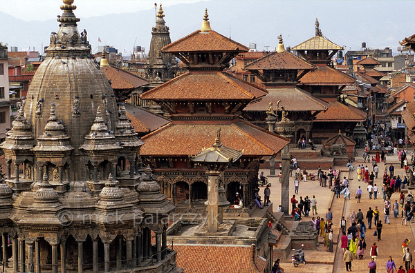 [NEPAL.KATHMANDUVALLEY 27306] 'Patan's Durbar Square.'  Patan's Durbar Square stands crowded with temples. In the foreground the octagonal Chyasin Dewal Temple (18th cent.) can be seen. Behind that tower the multiple roofs of the Hari Shankar Temple (1706, dedicated to Krishna and Vishnu), the Bishwanath Temple (1627, dedicated to Shiva) and the Bhimsen Temple (17th cent., dedicated to the patron god of the traders). Photo Mick Palarczyk.