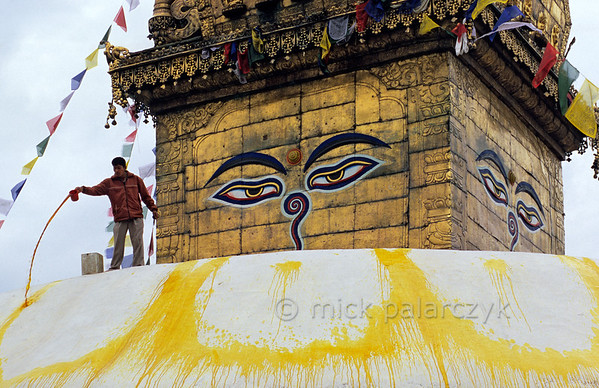 [NEPAL.KATHMANDUVALLEY 27209] 'Throwing paint at Swayambhu stupa.'  	Standing on the summit of Swayambhu stupa, west of Kathmandu, a boy is pouring yellow paint in curved patterns that resemble the petals of a lotus flower. According to the creation myth of the Kathmandu Valley, in ancient times a perfect lotus flower appeared on the lake which filled the Valley. Subsequently the lake was drained by a god and the lotus settled on top of a hill which was to become the location of the Swayambhu stupa. The all-seeing eyes of Adi-Buddha are attached to the gold gilded cube (harmika) that surmounts the stupa. Photo Mick Palarczyk.