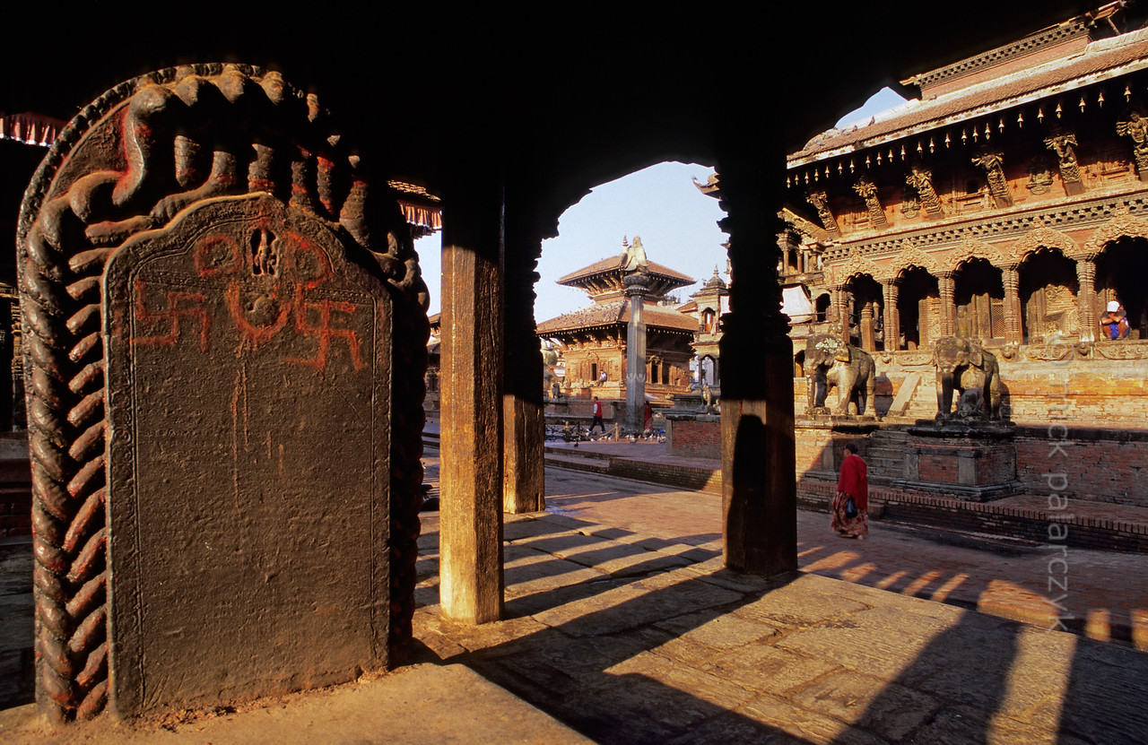 [NEPAL.KATHMANDUVALLEY 27323] 'Swastikas on royal throne.'  The Manimandapa pavilion (1701) on Patan's Durbar Square protects a royal throne from the elements. Seen here is the backside of the throne which is decorated with a royal inscription surrounded by snakes and two swastika's (holy Hindu symbols) in red powder. To the right the entrance to the Bishwanath Temple (dedicated to Shiva) is guarded by two elephants. Photo Mick Palarczyk.