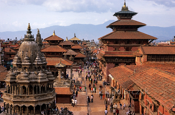 [NEPAL.KATHMANDUVALLEY 27301] 'Patan's Durbar Square.'  In the late afternoon sunlight the bricks of Patan's Durbar Square envelop the place in warm red glow. The eastern side of the square (to the right) is occupied by the buildings of the Royal Palace. In the left foreground the octagonal Chyasin Dewal Temple (18th cent.) can be seen, dedicated to Krishna. Behind that tower the multiple roofs of the Hari Shankar Temple (1706, dedicated to Krishna and Vishnu), the Bishwanath Temple (1627, dedicated to Shiva) and the Bhimsen Temple (17th cent., dedicated to the patron god of the traders). Photo Mick Palarczyk.