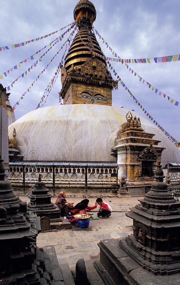 [NEPAL.KATHMANDUVALLEY 27215] 'Receiving a tika at Swayambhu.'  Surrounded by small shrines, at the foot of Swayambhu stupa, west of Kathmandu, a boy is receiving a tika. This dot on the forehead made with coloured powder, yogurt and rice must confer the blessing and protection of a deity. Photo Mick Palarczyk.