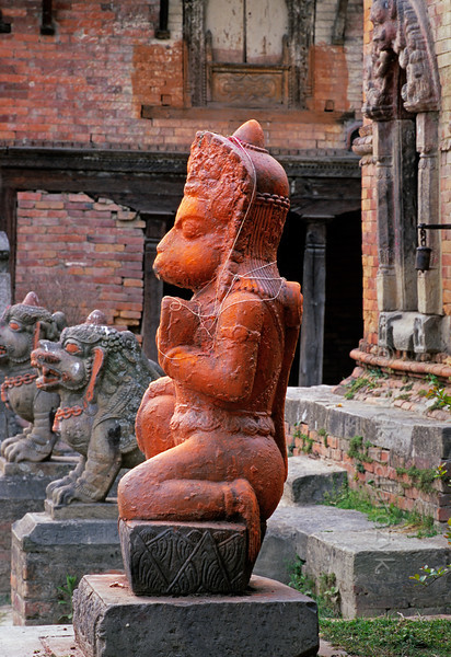 [NEPAL.KATHMANDUVALLEY 27414] 'Hanuman on Bhaktapur's Maheshwari Ghat.'  A statue of the Hindu ape-god Hanuman has been smeared with orange powder and decorated with holy threads as a result of puja offerings. The statue can be found on the Maheshwari Ghat along the Hanumante River in Bhaktapur. Owing to his ability to ward of evil spirits, Hanuman is one of the most popular gods in Nepal. Photo Mick Palarczyk.