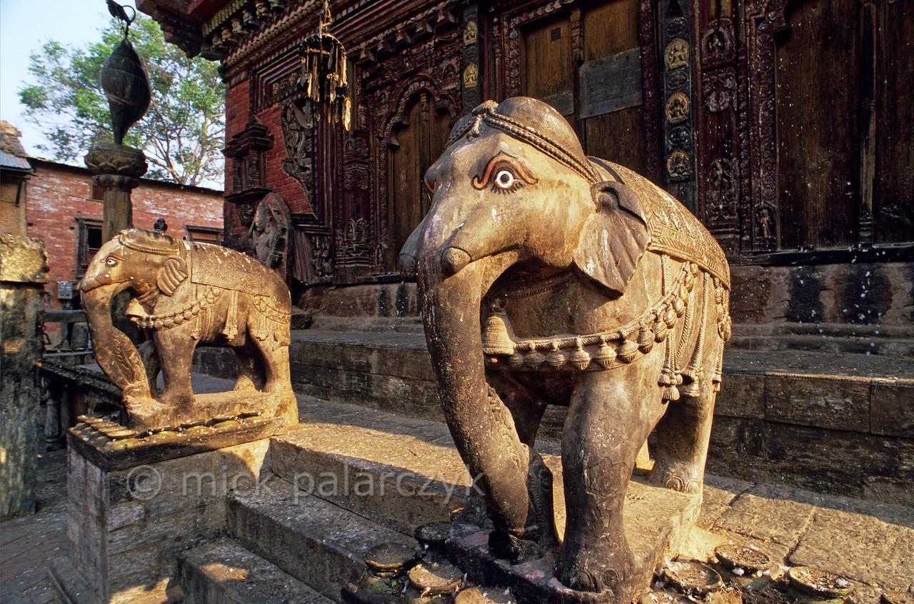 [NEPAL.KATHMANDUVALLEY 27542] 'Elephants at Changu Narayan.'  The southern entrance of the Vishnu Temple (ca. 1700) at Changu Narayan is guarded by two elephants. Photo Mick Palarczyk.