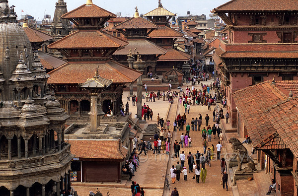 [NEPAL.KATHMANDUVALLEY 27302] 'Patan's Durbar Square.'  Patan's Durbar Square is the favourite spot for its citizens to saunter. The eastern side of the square (to the right) is occupied by the buildings of the Royal Palace. In the left foreground a part of the octagonal Chyasin Dewal Temple (18th cent.) can be seen. Behind that tower the multiple roofs of the Hari Shankar Temple (1706, dedicated to Krishna and Vishnu), the Bishwanath Temple (1627, dedicated to Shiva) and the Bhimsen Temple (17th cent., dedicated to the patron god of the traders). Photo Mick Palarczyk.