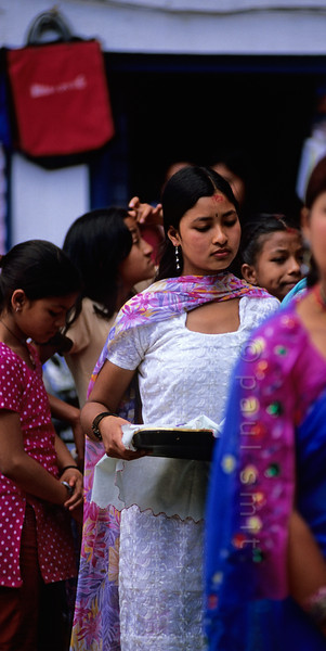 [NEPAL.KATHMANDUVALLEY 27506] 'Women in Thimi.'  On the first day of the Nepalese New Year the women of Thimi, dressed in their best clothes, are on their way to the Bal Kumari Temple with offerings of flowers, red powder and food. Photo Paul Smit.