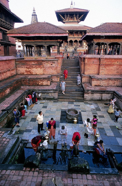 [NEPAL.KATHMANDUVALLEY 27330] 'Tapping water on Patan's Durbar Square.'  	In the early morning citizens tap water at Manga Hiti, a sunken well and watertank at the northern end of Patan's Durbar Square. The stairs to the tank are flanked by two pavilions, the right one of which houses a royal throne (see picture 27323). Behind the pavilions rises the Bishwanath Temple (dedicated to Shiva). Photo Mick Palarczyk.
