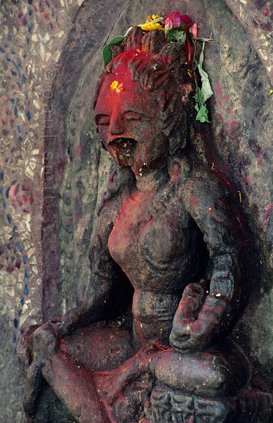 [NEPAL.KATHMANDUVALLEY 27422] 'Screaming goddess in Bhaktapur.'  This statue of Kali, Hindu Goddess of Destruction, on Bhaktapur's Hanuman Ghat (along the Hanumante River) has lost its lower jaw, giving the deity a particular freightening appearance. The goddess has received offerings of flowers and red powder. Photo Paul Smit.