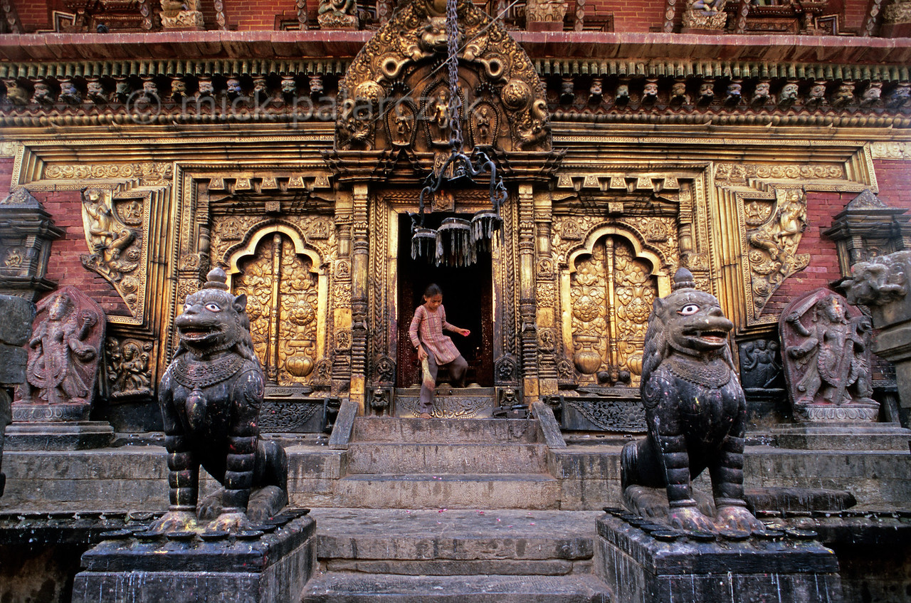 [NEPAL.KATHMANDUVALLEY 27545] 'Lions at Changu Narayan.'  A girl steps out across the high threshold of the Vishnu Temple (ca. 1700) at Changu Narayan after having swept the inner sanctum with her broom. This main (western) entrance of the temple is surrounded by copper repoussé work and guarded by two lions. An elaborate torana surmounts the gate. Photo Mick Palarczyk.