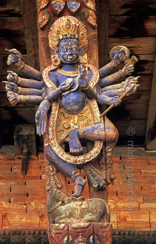 [NEPAL.KATHMANDUVALLEY 27313] 'Roof strut in Patan palace.'  Roof strut in the Mul Chowk courtyard of Patan's Royal Palace representing the Hindu God Bhairava. Bhairava is the fierce manifestation of Shiva, associated with annihilation and the march of time. Bhairava beheaded one of Brahma's five heads and as punishment was forced to carry around the skull as a beggar's nap. Photo Mick Palarczyk.