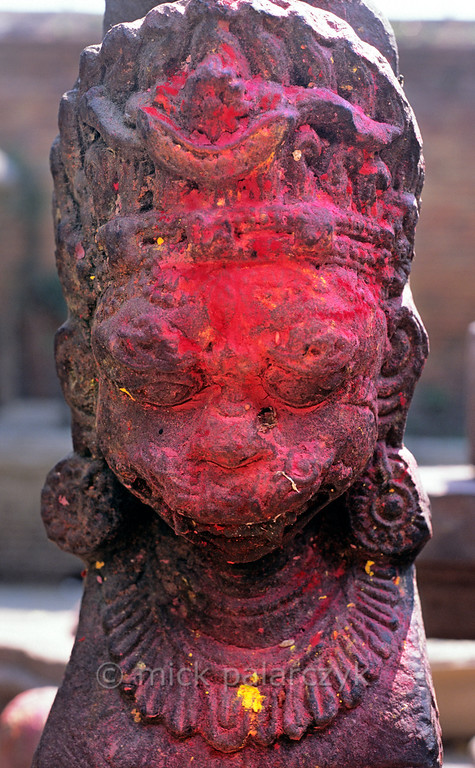 [NEPAL.KATHMANDUVALLEY 27413] 'Bhairava in Bhaktapur's Wakupati Temple.'  The coloured powder on this statue of Bhairava in the courtyard of Bhaktapur's Wakupati Narayan Temple has been smeared across its face by the rain. Bhairava is the fierce manifestation of Shiva, associated with annihilation and the march of time. He can be identified here by his bulging eyes, his mustache and the crescent moon of Shiva in his hair. Photo Mick Palarczyk.