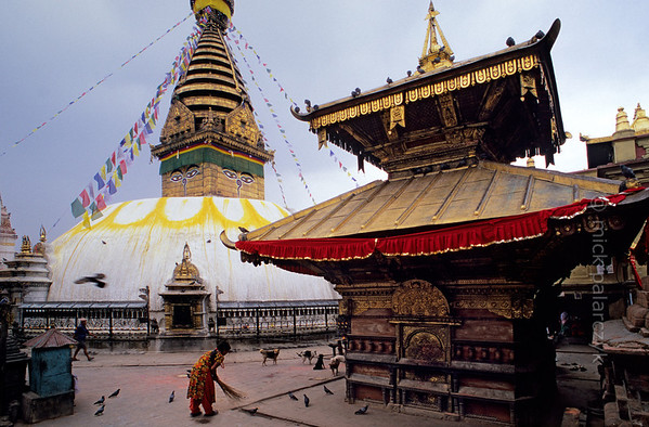 [NEPAL.KATHMANDUVALLEY 27217] 'Harati Temple at Swayambhu.'  At the foot of Swayambhu stupa, west of Kathmandu, a woman is sweeping the pavement around the gilt-roofed Temple of Harati. This goddess, also known as Ajima, is revered as a protectress against childhood diseases. Photo Mick Palarczyk.